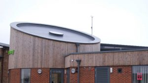 Wymondham Library: Curved Meridian Aluminium Wall Coping, Aluminium Eaves System with hidden gutter & support-work, Rainwater pipes & Brise Soleil Shading System