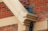 Justice Court: Stone Corbel Profile Fascia Soffit System in Stone-effect ppc with Hidden gutter & Contemporary Diameter Rainwater Pipes